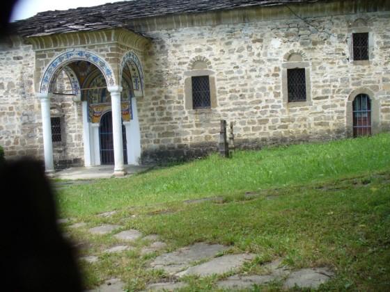 Поглед през дървената порта към църквата