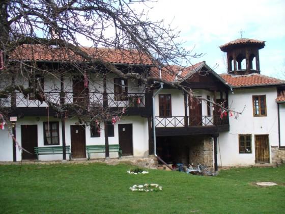 Двор на манастира с красиво дърво, окичено с мартеници